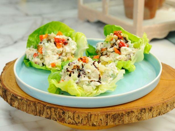 Куриный салат с клюквой и орехами на салатных листьях
