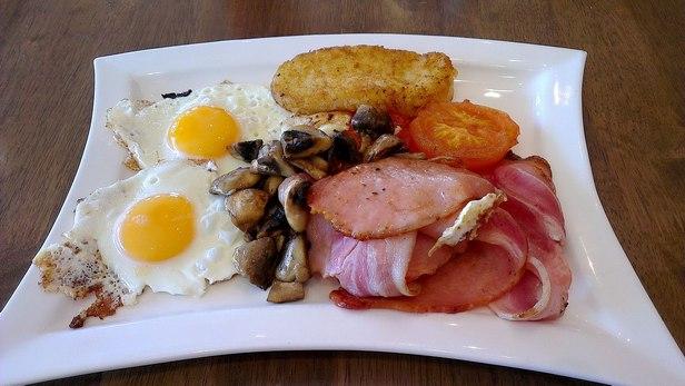 Фото Ирландский завтрак с яичницей, картофельными оладьями и печеными томатами