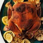 Целая курица, натертая специями, с печеным чесноком и лимонами