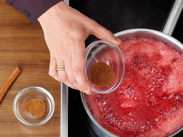 Смешайте клюкву, сахар и апельсиновый сок в большом сотейнике