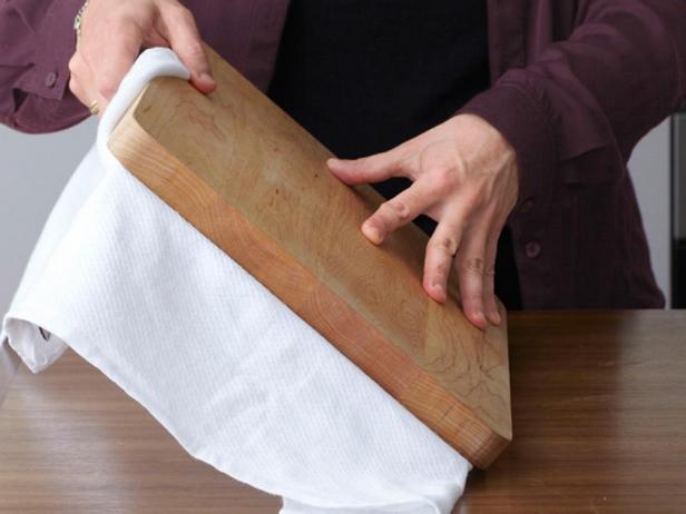 Удерживая разделочную доску, переверните вместе с противнем.