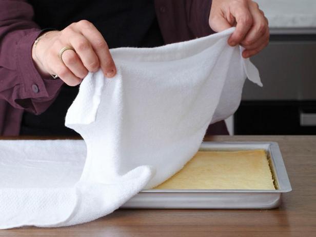 Пока корж еще теплый, положите сверху слегка влажное кухонное полотенце