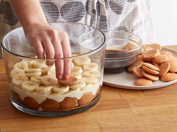 Поверх печенья, чередуя, выкладывайте слои пудинга и бананов
