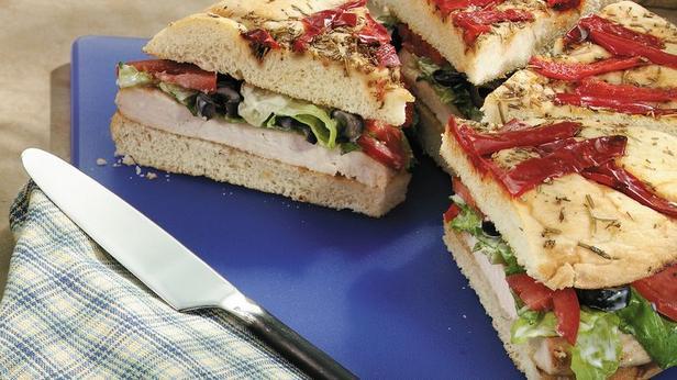 Фото Сэндвич из лепешки фокачча с маринованной курицей и спредом из шпината и артишоков