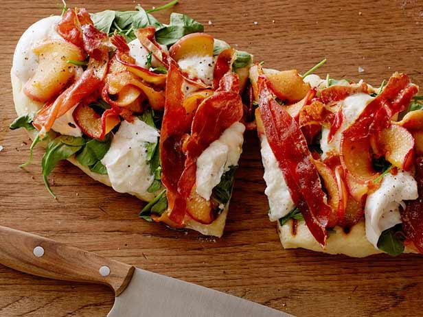 Фото Летняя пиццетта с персиками, сыром буррата, рукколой и хрустящей ветчиной на гриле