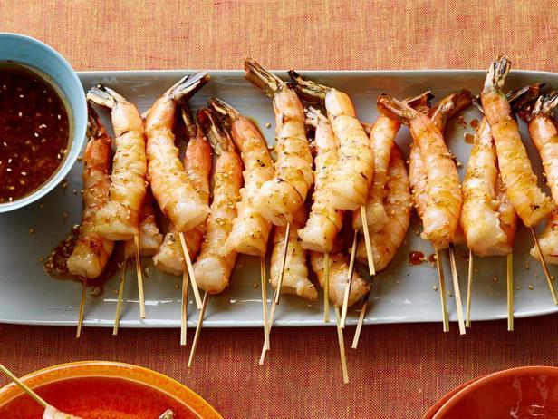 Жареные креветки на шампурах с соевым соусом, свежим имбирём и поджаренным кунжутом