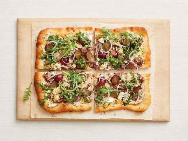 Фото Пицца с колбасным фаршем, руколой и виноградом