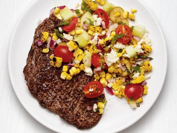 Фото Жареный стейк с греческим салатом с кукурузой