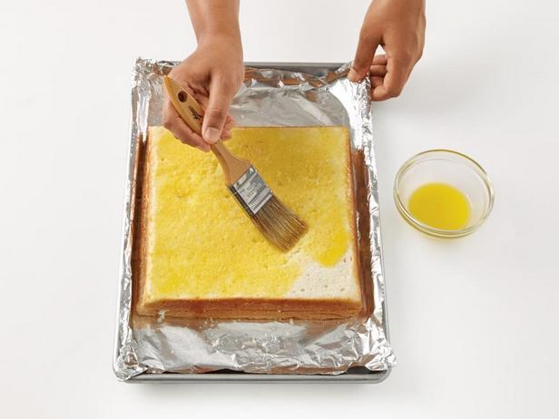 Смажьте верхний корж растопленным сливочным маслом
