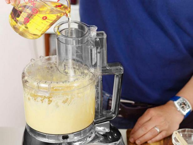 Загрузите в кухонный комбайн ингредиенты для соуса и влейте масло