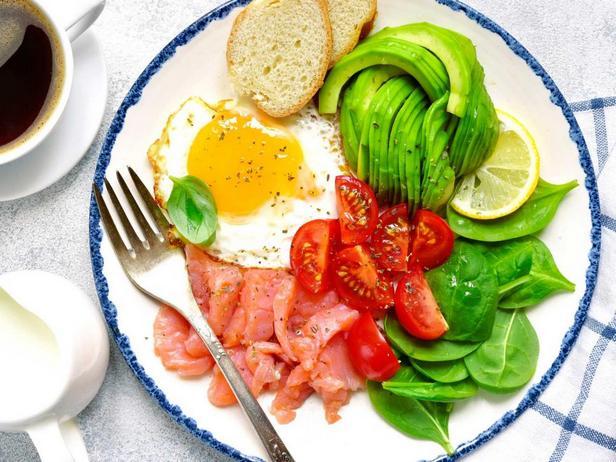 Полезный завтрак с яичницей, авокадо, салатом, лососем и кофе с молоком